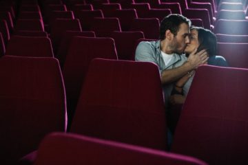 Couple kissing in an empty movie theatre