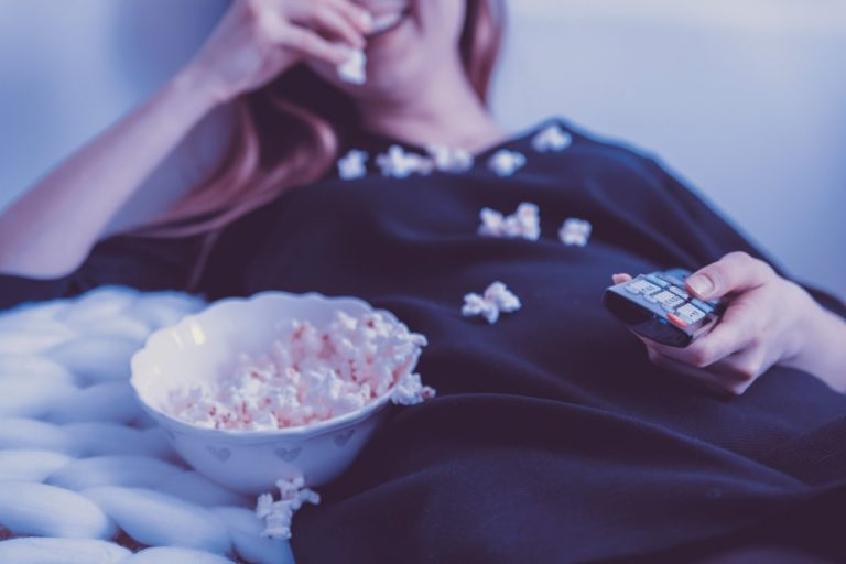 Mulher a ver TV e comer pipocas