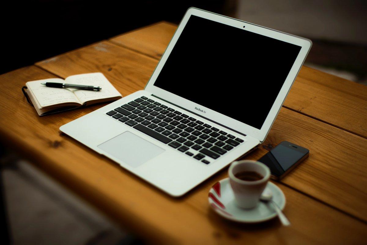 MacBook Air, iPhone 4, um caderno e uma chávena de café numa mesa de madeira