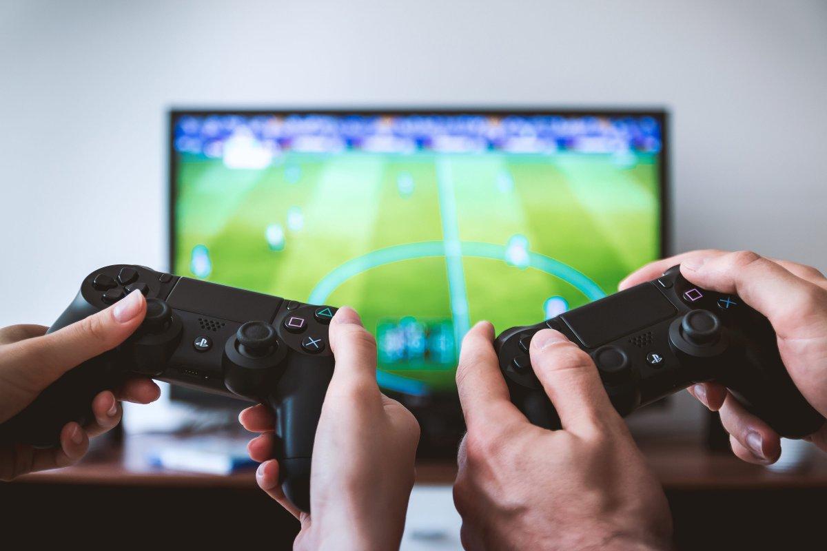 Dois comandos de PS4 a jogar FIFA